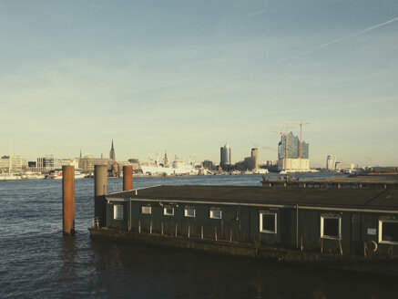 View on the construction of Elbphilharmony across the river Elbe, warehouse in front, Hamburg, Germany - SE000359