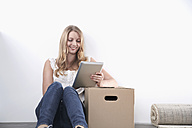 Smiling young woman with cardboard box and tablet computer - PDF000604