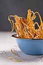 Bowl of uncooked chili pasta with chili pods and chili threads on white wooden table - MYF000109