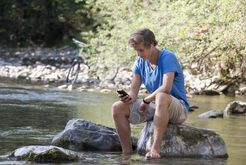 Austria, Salzkammergut, Mondsee, young man with mobile phone relaxing at a brook - WWF003191