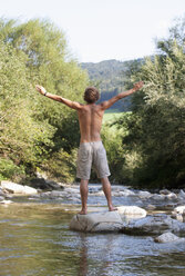 Austria, Salzkammergut, Mondsee, young man with outstretched arms standing at a brook - WWF003199