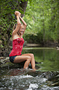 Austria, Salzkammergut, Mondsee, teenage girl refreshing at a brook - WWF003203