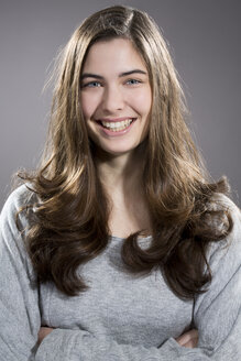 Portrait of smiling young woman, studio shot - MAEF007612
