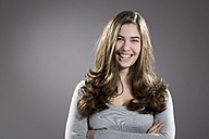 Portrait of smiling young woman, studio shot - MAEF007616