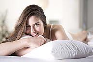 Smiling young woman with pillow lying on bed - MAEF007629