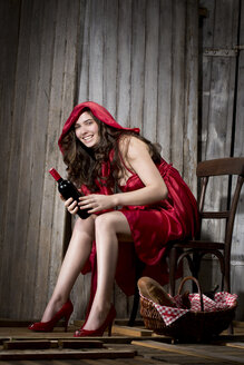 Young woman sitting in a shack dressed as Red Riding Hood, studio shot - MAEF007588