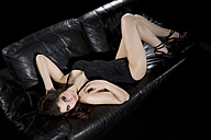 Young woman wearing black bathing suit and high heels lying on black leather couch - MAEF007637