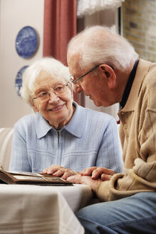 Senior couple watching old photographs at home - BIF000270