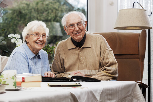 Senior couple watching old photographs at home - BIF000282
