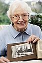 Senior women showing old photograph of herself - BIF000275