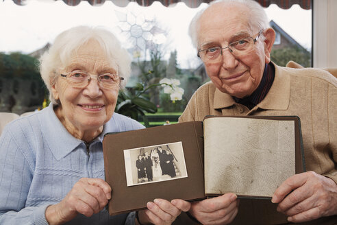Senior couple showing old photograph of  wedding day - BIF000278