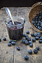 Wickerbasket with blueberries (Vaccinium myrtillus) and glass of blueberry jam on wooden table - LVF000431