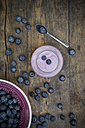 Blueberries (Vaccinium myrtillus), spoon and glass of blueberry yoghurt on wooden table - LVF000426