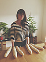 Young woman standing behind table with bread fingers, Picasso parody, Duesseldorf, NRW, Germany - MFF000709