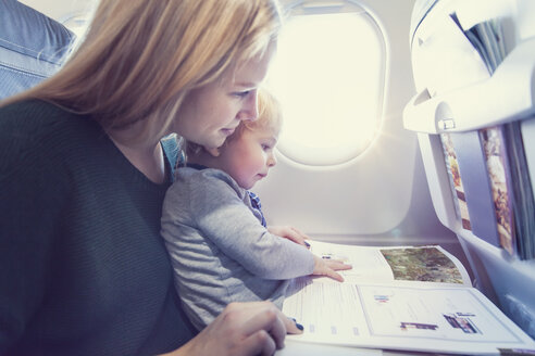 Mother with son in airplane reading magazine - MF000727