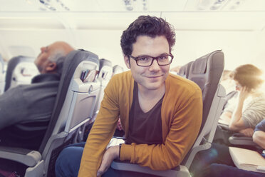 Smiling man in airplane, portrait - MF000728