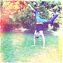 In the garden, woman does a cartwheel, North Rhine-Westphalia, Germany - ONF000381