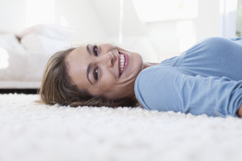 Portrait of smiling woman lying on a carpet - RBF001515