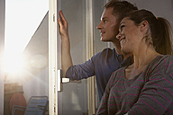 Couple standing at open window - RBF001536