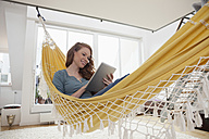Smiling woman relaxing with tablet computer in a hammock in her apartment - RBF001547