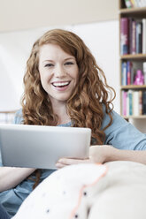 Portrait of young woman relaxing with tablet computer on a couch in her apartment - RBF001556