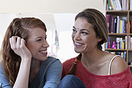 Two young female friends at home exchanging confidences - RBF001569