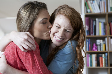 Two young female friends at home embracing - RBF001571