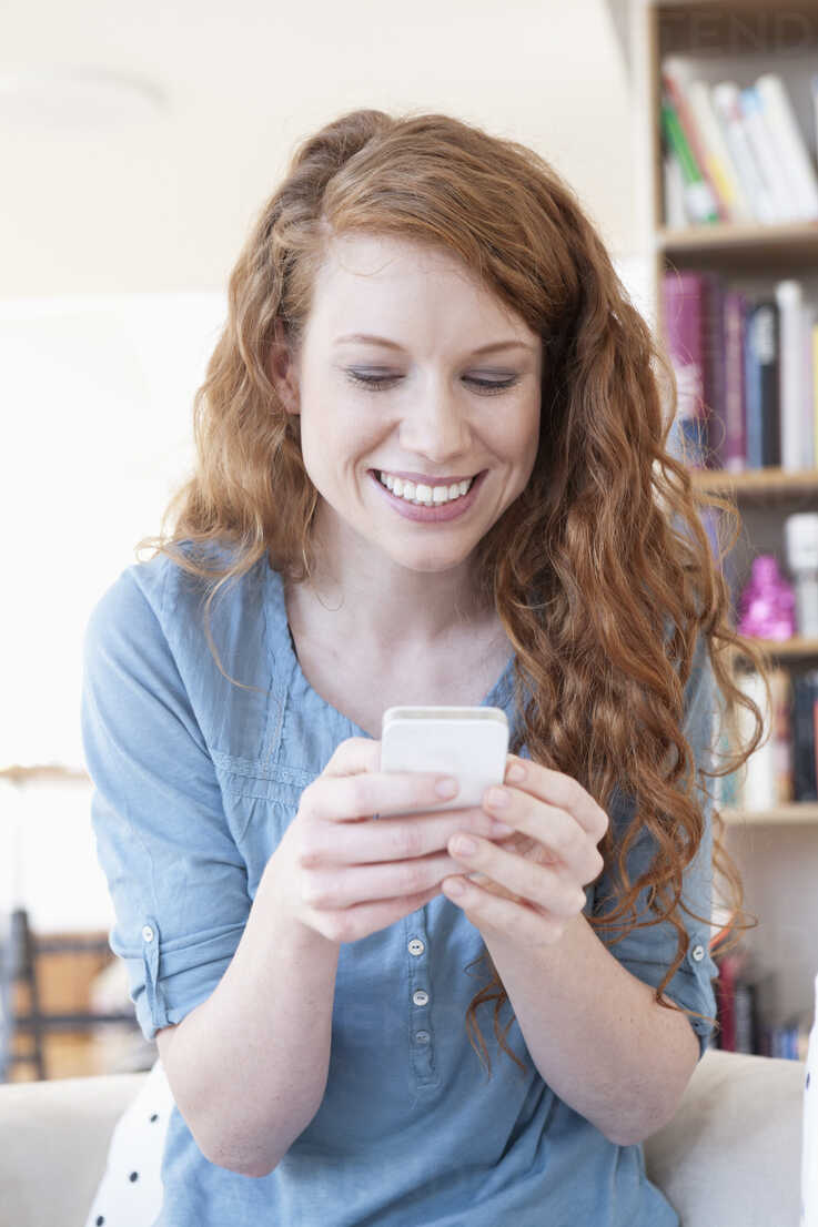 Young woman using smartphone at home - RBF001574 - Rainer Berg/Westend61