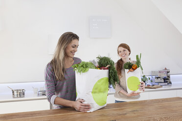 Two women holding shopping bags with purchases - RBF001595