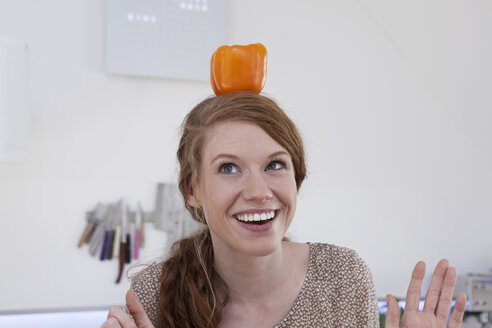 Young woman balancing orange bell pepper on her head - RBF001519