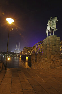 Germany, North Rhine-Westphalia, Cologne, lighted Cologne Cathedral and Hohenzollern Bridge with monument of Wilhelm I at night - JATF000550