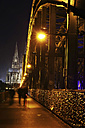 Germany, North Rhine-Westphalia, Cologne, lighted Cologne Cathedral and Hohenzollern Bridge with pedestrians at night - JATF000551