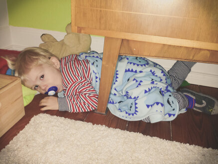 Little boy sick, laying under cupboard with sucker and monster blanket - MEAF000058