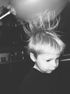 Little boy's hair being pulled up by static powers of balloon - MEAF000102