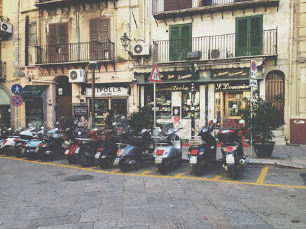 Row of scooters standing before houses in Palermo, Sicily, Italy - MEA000086