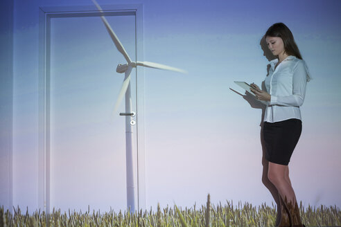Young woman with projection of wind turbine using digital tablet - BGF000056