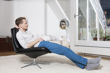 Man relaxing in armchair after work - RBF001496