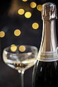 Champagne glass and bottle in front of lights, close-up - SBDF000456