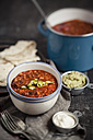 Tortillas and bowls of guacamole, sour cream, Chili con carne on wooden table - SBDF000460