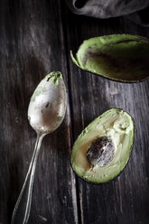 Kitchen towel, spoon and sliced and hollowed halfs of an avocado on wooden table - SBDF000465