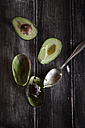 Spoon and sliced and hollowed halfs of two avocados on wooden table - SBDF000469