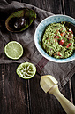 Bowl of guacamole, kitchen towel, pestle, sliced lime and hollowed half of avocado on wooden table - SBDF000470