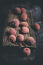 Lychees and board on dark wooden table - SBDF000440