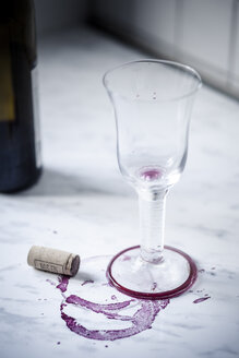 Empty red wine glass, bottle, stains and wine cork on white marble - SBDF000452