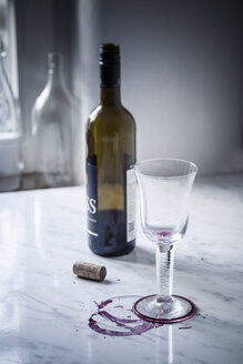 Empty red wine glass, bottles, stains and wine cork on white marble - SBDF000473