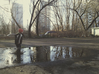 Little boy jumping into the puddle. Berlin, Germany. - ZMF000095