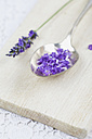 Blossom and petals of lavender (Lavendula) on spoon and wooden board, close-up - GWF002484