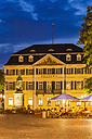 Germany, North Rhine-Westphalia, Bonn, view to Muensterplatz with street cafe at evening twilight - WD002194