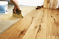 Man applying glue for laying finished parquet flooring, close-up - BIF000308