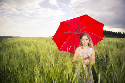Germany, teenage girl with red umbrella standing in a corn field - VTF000062